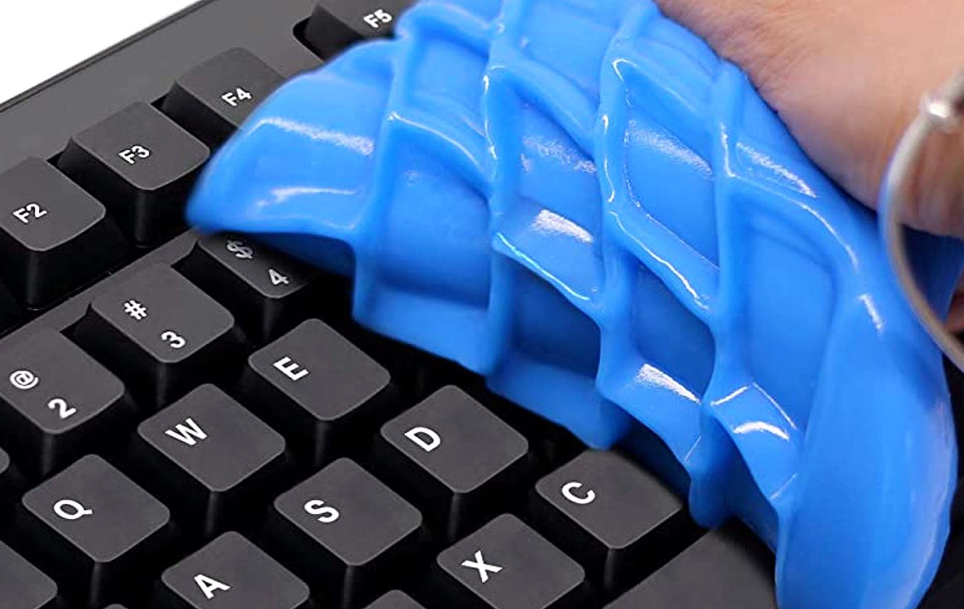 Blue keyboard cleaning gel being removed from a black mechanical keyboard.