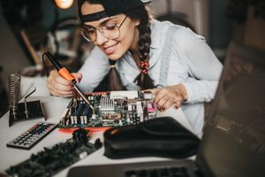 Woman working on a computer motherboard.