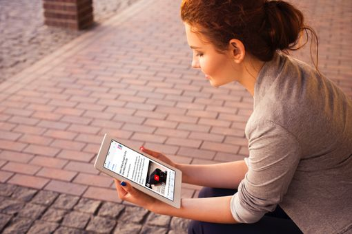 A person reading news on an iPad sitting outside,