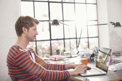 Data analyst working on laptop near large window