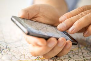 Photo of a pair of hands holding a smartphone on top of a paper map.
