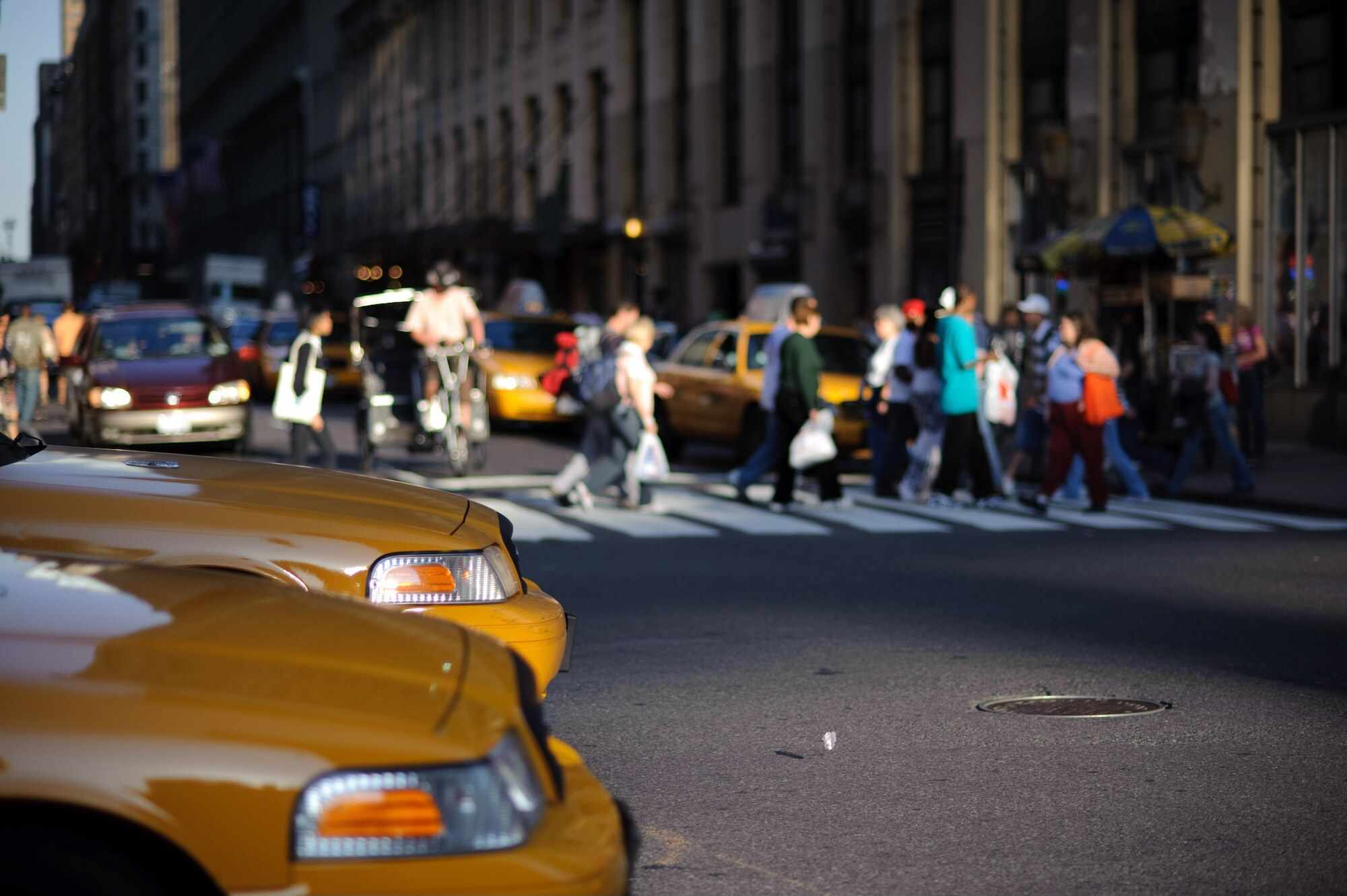Pair of taxis waiting at an intersection while people cross the street in the background