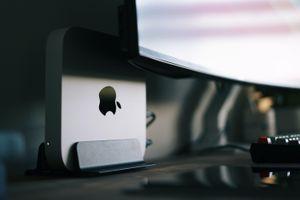 M1 Mac mini setup behind a monitor on a desk