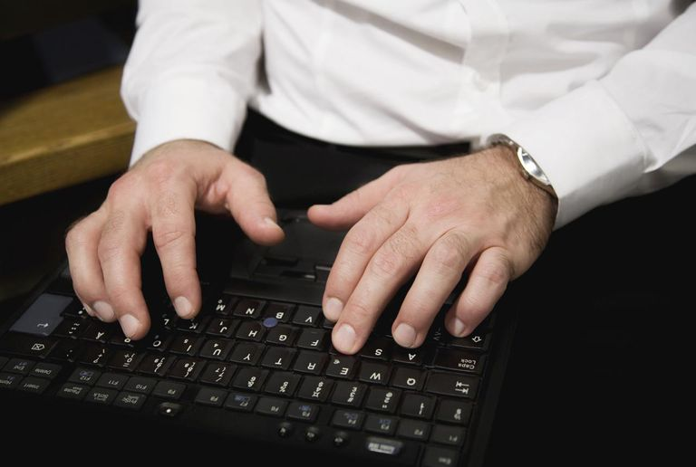 Close-up of business man typing on laptop