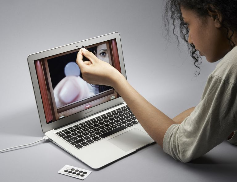 A woman covering her laptop webcam