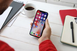 A person sitting at a table with a cup of coffee, holding an iPhone X. The screen of the iPhone X shows a variety of app icons.