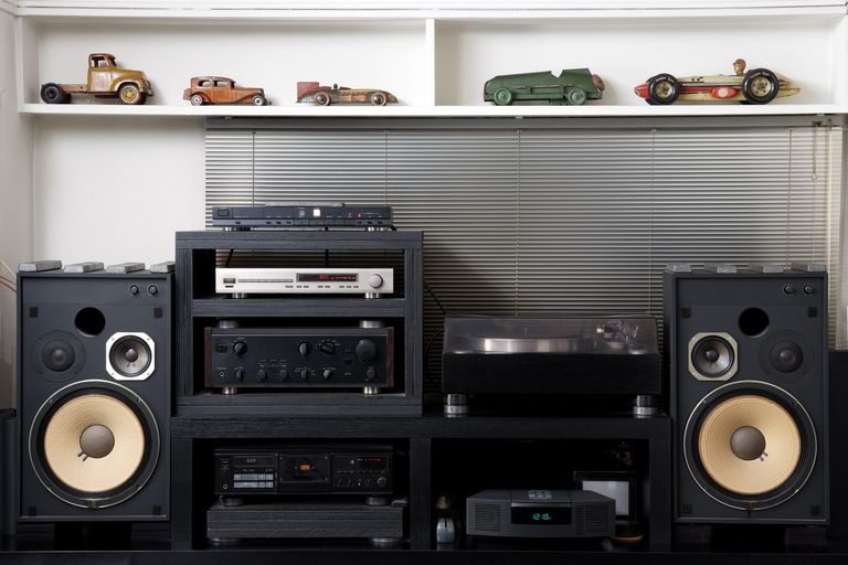 A Hi Fi Sound System Underneath Shelf Lined With Vintage Toy Cars