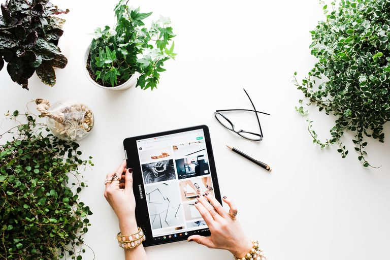Woman using tablet surrounded by plants
