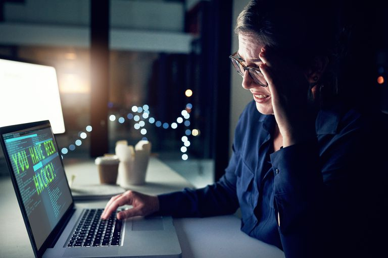 An upset person looks at a laptop screen which displays 'you have been hacked' on it.