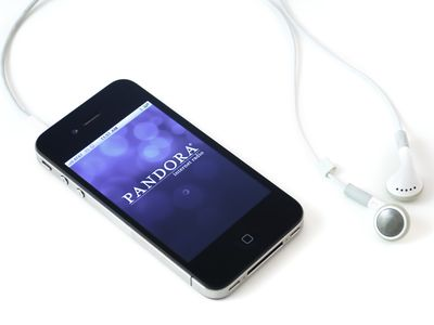 Earbuds and phone screen showing Pandora application