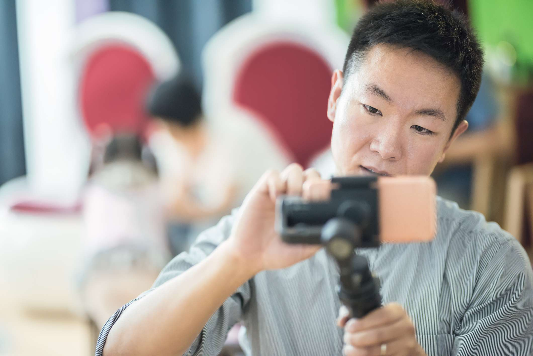 Someone using a smartphone on a tripod stabilizer to take photos.