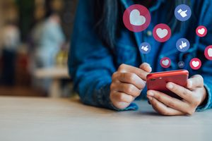 Woman using smartphone with heart and thumbs-up icons swirling around