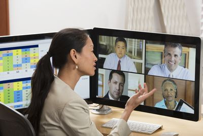 A woman participating in a video conference on her computer