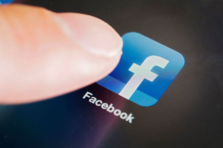 finger touching facebook icon on mobile device