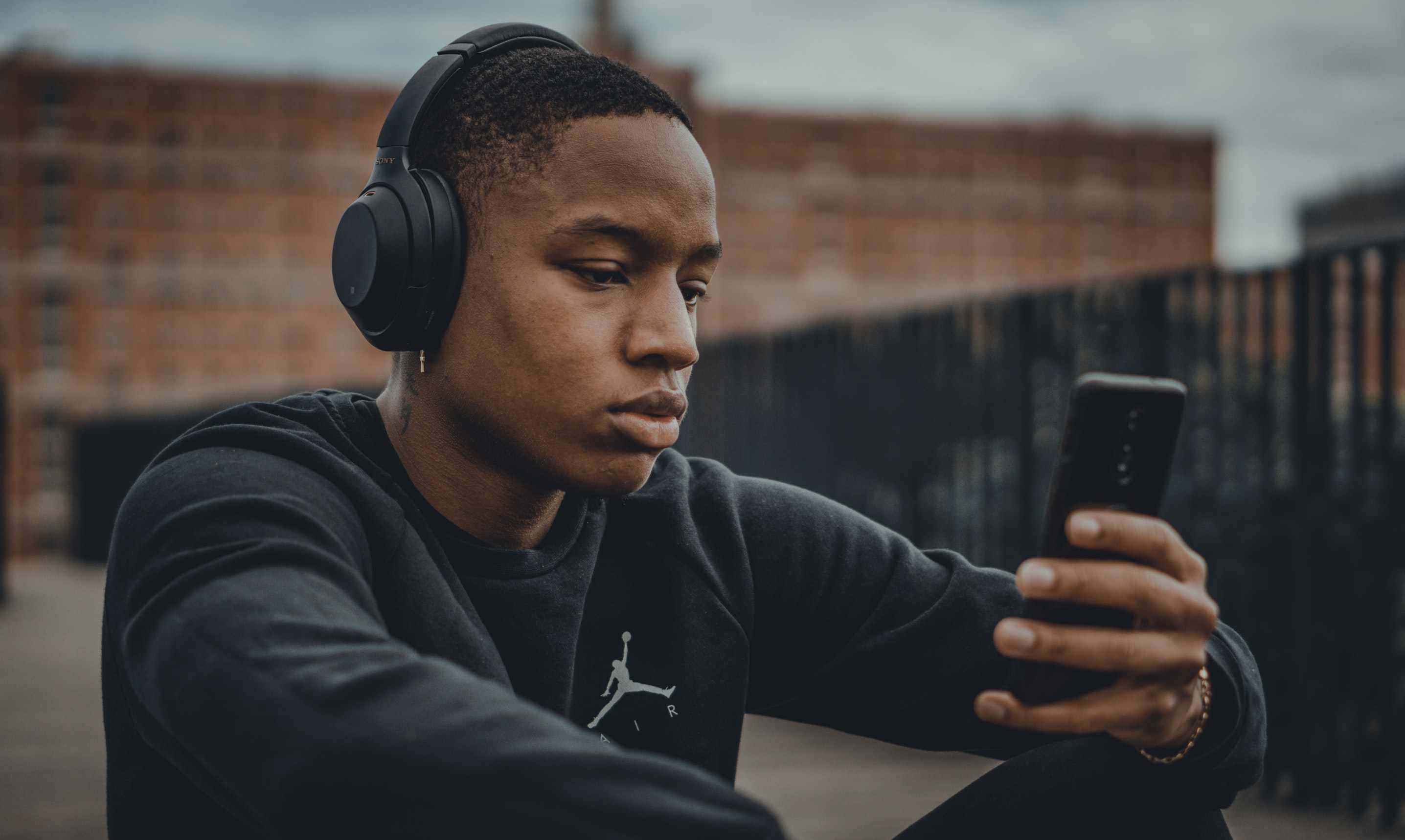 man wearing black nike sweater while wearing headphones and listening to their phone
