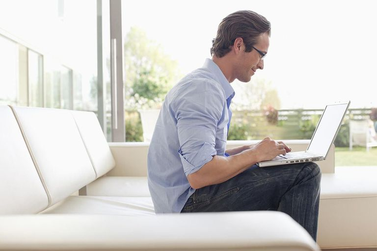 Man sitting on sofa on patio using laptop