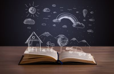 Book open on a table with an illustration of a couple standing next to a house and a car under a rainbow over the book