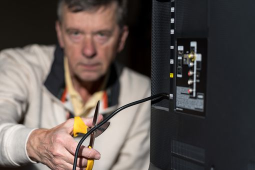 A man cutting the cable cord on a television.