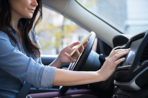 woman in car holding cell phone programming journey
