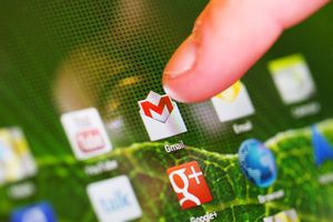 finger about to touch Gmail logo on mobile device