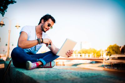Person sitting on a ledge using an iPad