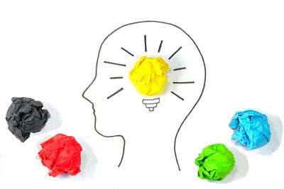 Concept of Creative Ideas and Innovation. Bulb glowing inside human head with crumpled papers around.