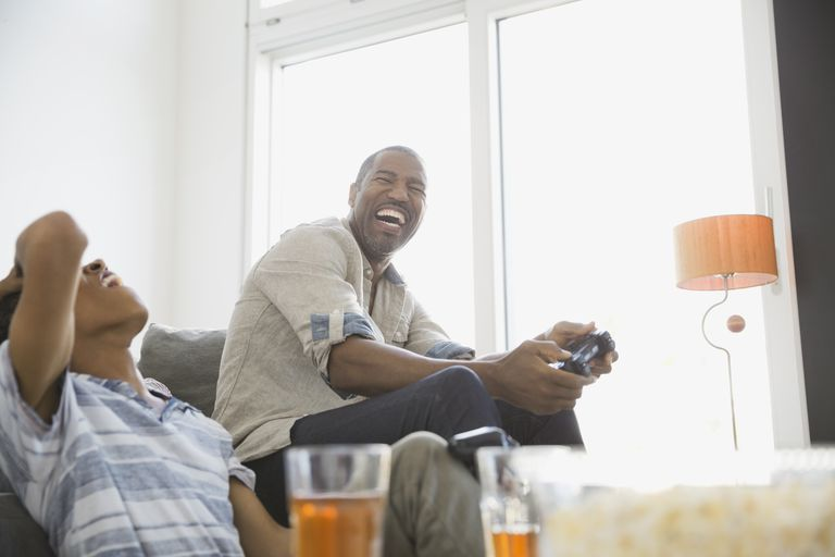 Father and son playing video games at home, laughing