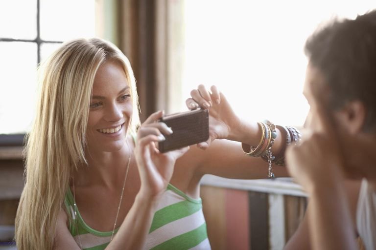 Young woman taking picture with cell phone