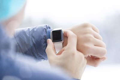 Figure wearing and looking at Apple Watch on wrist
