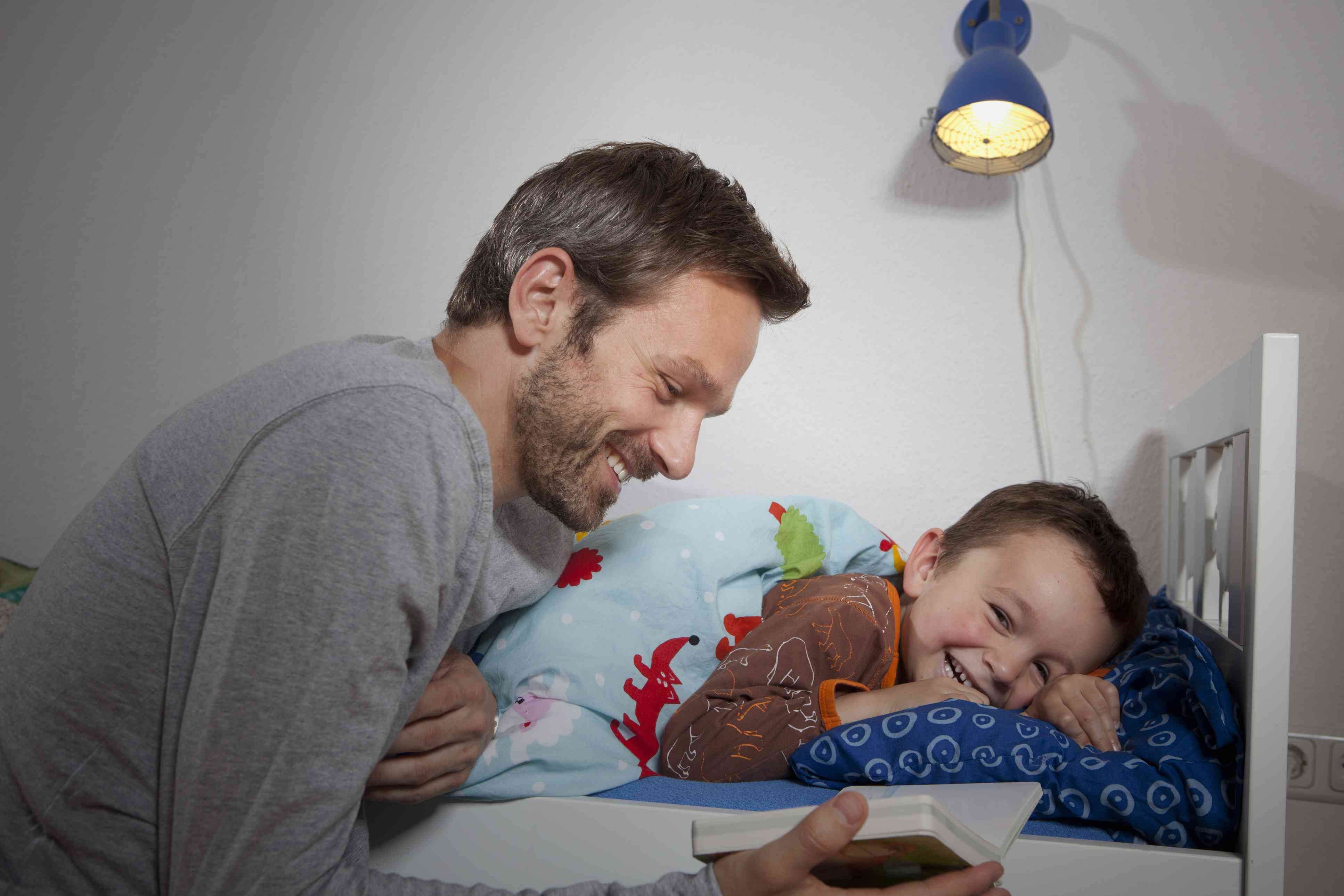 Father reading a story to son at bedtime.