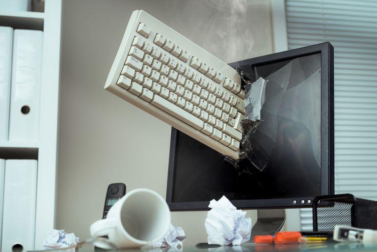 A keyboard thrown through a computer monitor