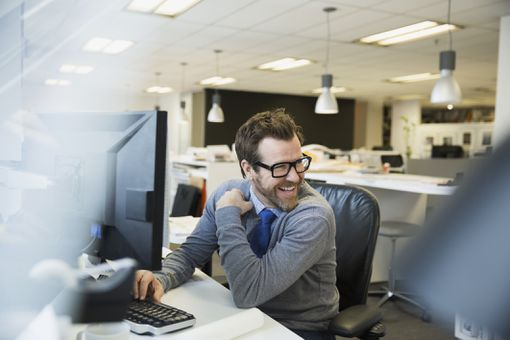 Man wearing glasses and using his computer while laughing