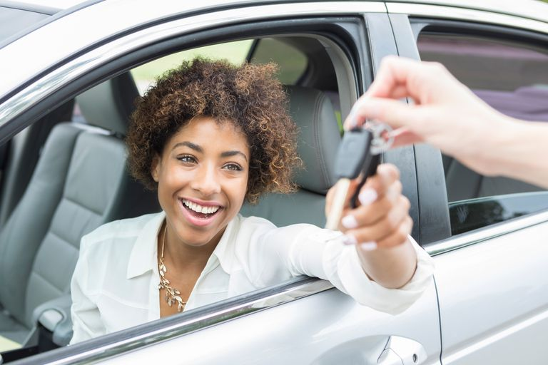 A woman accepting the keys to a car she's purchased.