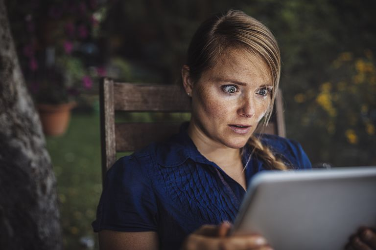 Woman in backyard looking at a tablet, shocked