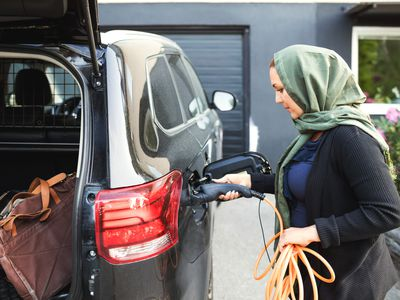 Woman charging her electric vehicle at home