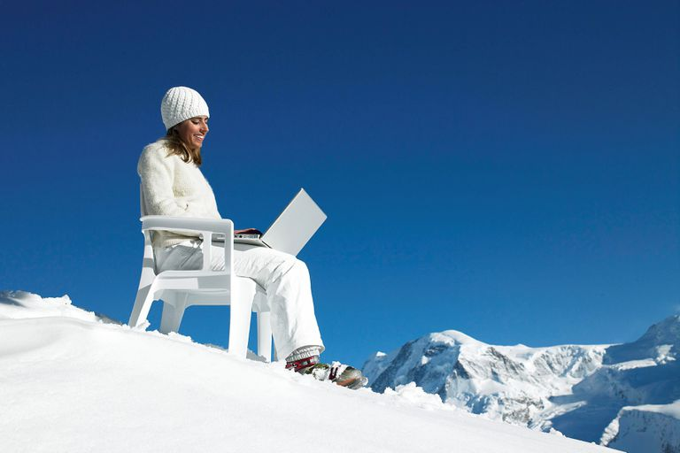 Person on snowy mountain sitting in plastic chair using laptop