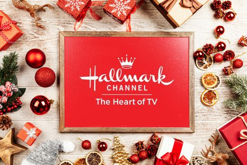 The Hallmark Channel logo in a picture frame surround by Christmas ornaments