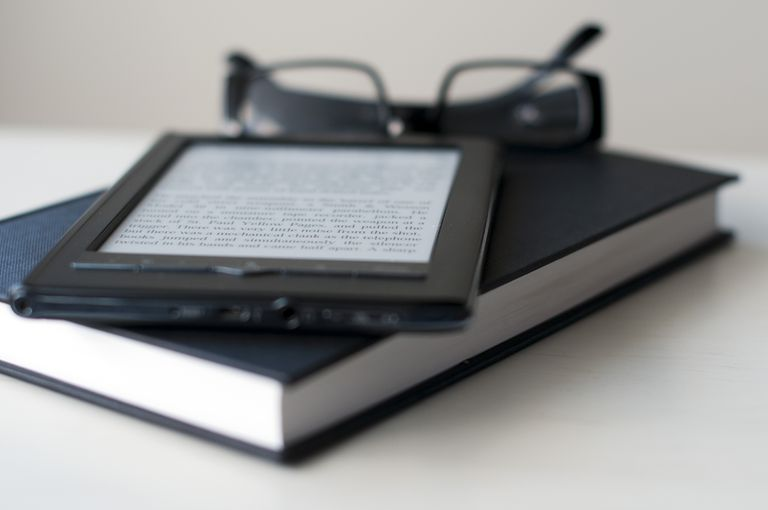 E-reader amazon kindle on top of a book next to glasses