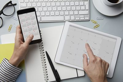 A view of a desk surface with a smartphone displaying a calendar app, and a tablet also displaying a calendar app.