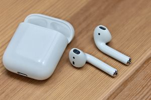 Apple AirPods and charging case on a table.
