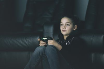 A young girl holding a games controller sitting against a sofa